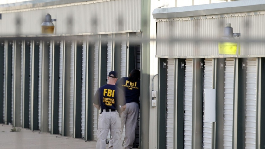"Authorities search a storage unit at Gibson Self Storage as they continue to investigate the slayings of Kaufman County District Attorney Mike McLelland, his wife and a top prosecutor, Saturday, April 13, 2013 in Seagoville, Texas. Authorities investigating the death of a Texas district attorney arrested Eric Williams, a former justice of the peace and charged him Saturday with making a ""terroristic threat"" after searching his home. (AP Photo/The Dallas Morning News, Michael Ainsworth)  MANDATORY CREDIT; MAGS OUT; TV OUT; INTERNET USE BY AP MEMBERS ONLY; NO SALES"
