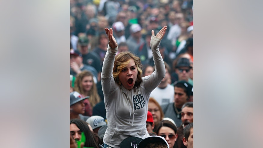 Members of a crowd numbering tens of thousands smoke marijuana and listen to live music, at the Denver 420 pro-marijuana rally at Civic Center Park in Denver on Saturday, April 20, 2013. Even before the passage in November 2012 of Colorado Amendment 64 promised the legalization of marijuana for recreational use, April 20th has for years been a celebration of marijuana counterculture, and the 2013 Denver rally draw larger crowds than previous years. (AP Photo/Brennan Linsley)