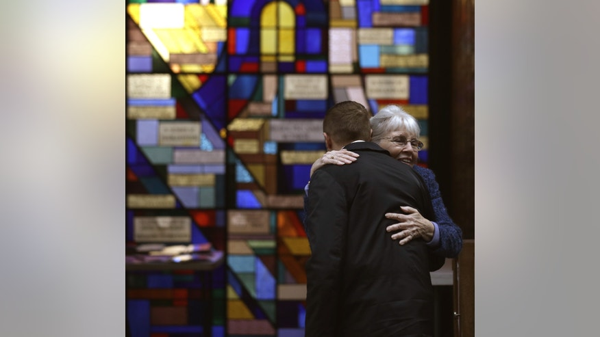 Sue Haff, right, a member of Trinity Episcopal Church in Boston, greets a man arriving at Temple Israel, which allowed the Trinity congregation to hold Sunday service, Sunday, April 21, 2013, in Boston. Trinity is within the blocked-off area near the finish line of the Boston Marathon, where earlier in the week two bombs exploded. (AP Photo/Julio Cortez)