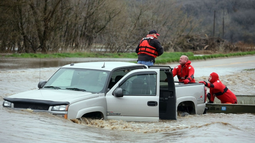 Members of the Burlington, Iowa, Fire Department Ky Duttlinger, center, and Greg Higdon, right, rescue Mike Schnedler, Burlington, from the back of his  pickup truck, Thursday April 18, 2013, after it was swept off of Flint Bottom Road in Burlington, Iowa.   Schnedler attempted to drive through the standing water covering the road. (AP Photo/The Hawk Eye, John Lovretta)