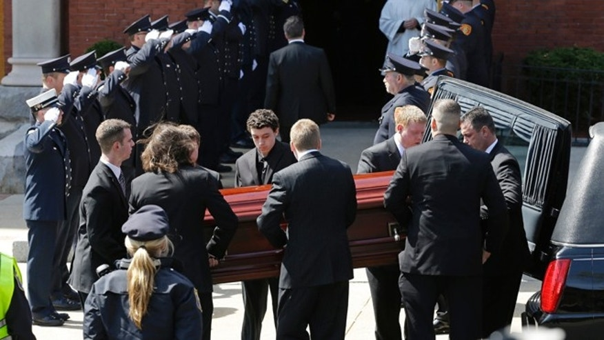 April 22, 2013: An honor guard from area fire departments salute as pallbearers carry the casket of Boston Marathon bomb victim Krystle Campbell, 29, into St. Joseph's Church for her funeral in Medford, Mass.