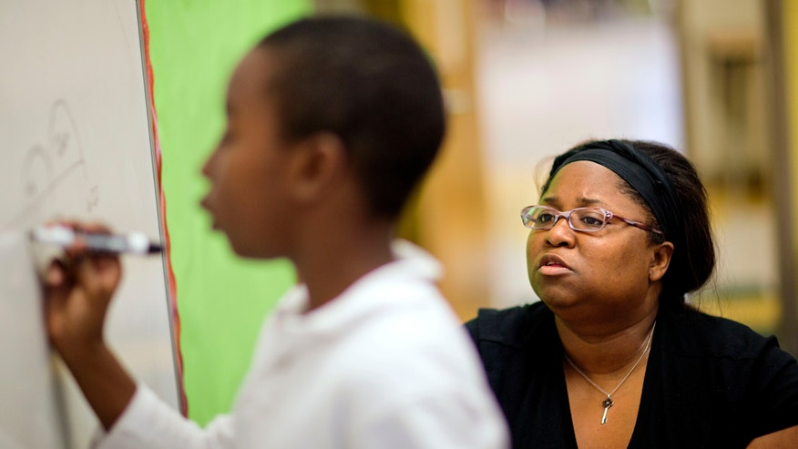 In this Thursday, April 18, 2013 photo, Burgess-Peterson Elementary School  student teacher Nicole Devoe, right, watches as third grader Samson Hall, works through a lesson as part of Atlanta Public School's after-school remediation program in Atlanta. Anxiety is high among students and teachers with state standardized tests set to begin Tuesday. A lot of focus and criticism has been aimed at the tests, known as CRCT in Georgia, since one of the nation's largest cheating scandals erupted within the Atlanta Public Schools system a few years back that included allegations that teachers and principals changed scores to inflate performance. While criminal charges are pending against 35 former Atlanta educators, the district has been working on a system-wide remediation program aimed at helping those directly affected by the cheating scandal and others who have simply fallen behind. (AP Photo/David Goldman)