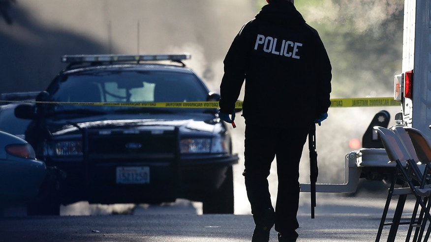 A police officer carries a shotgun and what appears to be a shell casing as officers collect evidence from the scene of an overnight shooting that left five people dead, including a suspect who was shot by arriving officers, at an apartment complex in Federal Way, Wash., early Monday, April 22, 2013. Federal Way Police Cmdr. Kyle Sumpter confirmed Monday that the shotgun pictured was used by the suspect in the shooting. (AP Photo/Ted S. Warren)