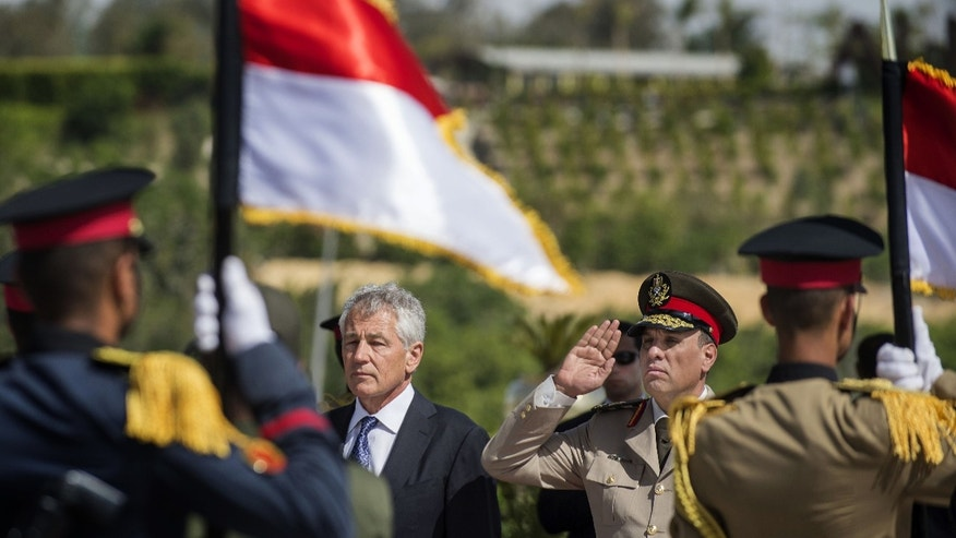 U.S. Secretary of Defense Chuck Hagel, center left, stands with an Egyptian army official before laying a wreath at the Tomb of the Unknown Soldier in Egypt's capital, Cairo on Wednesday, April 24, 2013. By including Cairo on his first Mideast tour as defense secretary, Chuck Hagel is highlighting the Obama administration's hope of preserving influence with the Egyptian military as the country struggles with its transition to democracy.(AP Photo/Jim Watson, Pool)