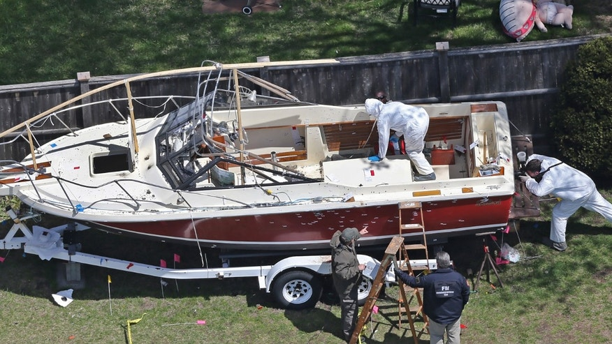 Investigators from the FBI inspect the boat where Boston Marathon bombing suspect Dzhokhar Tsarnaev was found hiding on Friday night in a backyard in Watertown, Mass., Tuesday, April 23, 2013. There is blood spattered on the wheel fender of the trailer and bullet holes in the hull of the boat. Tsarnaev had gunshot wounds to the head, neck, legs and hands when he was captured hiding out in the boat on Friday night, April 19, 2013. (AP Photo/The Boston Globe, David L. Ryan)  BOSTON HERALD OUT; QUINCY OUT; NO SALES
