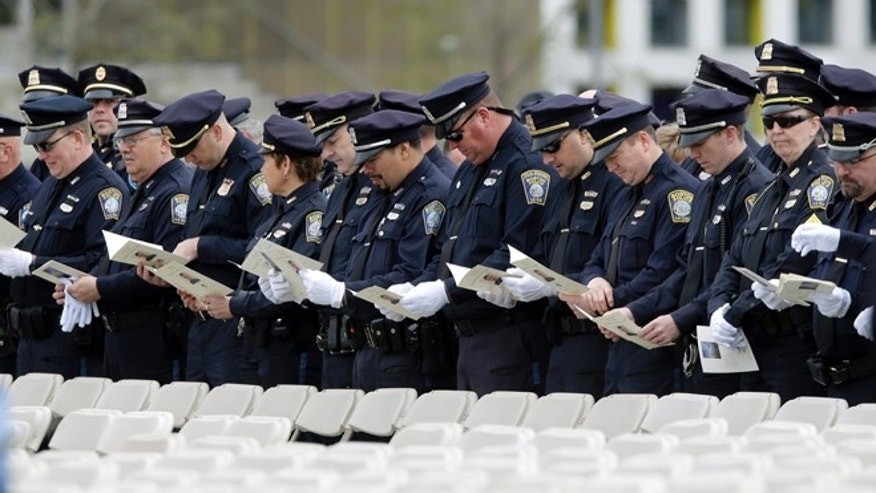 April 24, 2013: Police officers look at the program notes as they arrive to a memorial service for fallen Massachusetts Institute of Technology campus officer Sean Collier at MIT in Cambridge, Mass.  Authorities think the 27-year-old Collier was shot and killed by the Boston Marathon bombing suspects last Thursday.   (AP)