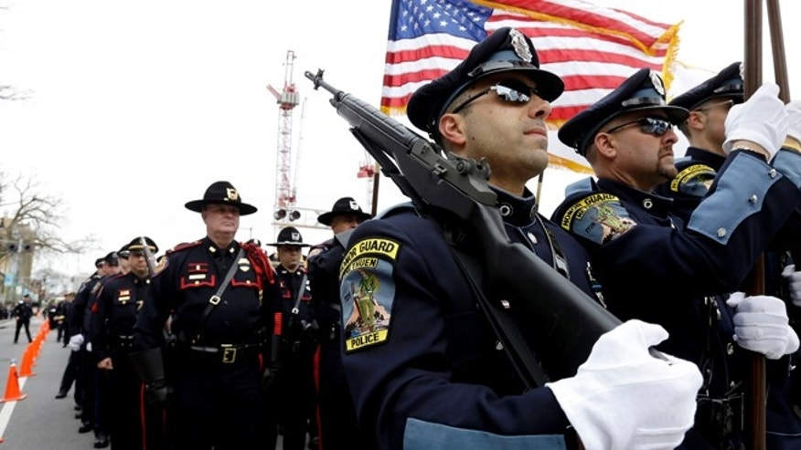 April 24, 2013: Members of a police honor guard, front, lead a column of law enforcement officials into a memorial service for fallen Massachusetts Institute of Technology police officer Sean Collier in Cambridge, Mass. Collier was fatally shot on the MIT campus on April 18. Authorities allege that the Boston Marathon bombing suspects were responsible. (AP)