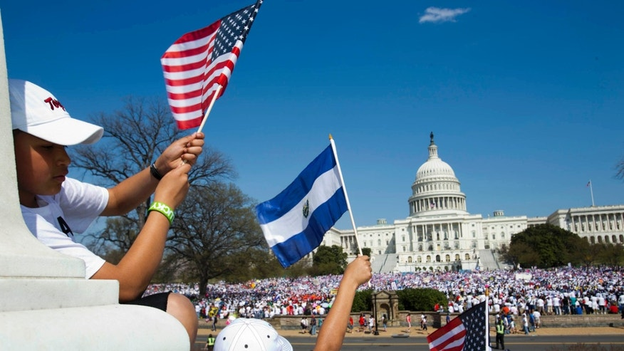 "FILE - In this April 10, 2013, file photo Cristian Paniagua, 11, of Takoma Park, Md., left, holds a U.S. flag next to a child holding the flag of El Salvador during a ""Rally for Citizenship"" on Capitol Hill in Washington. Our leaders always play politics after catastrophe, whether made by man or Mother Nature. After the Boston bombings Republicans argued that the role of two immigrant suspects in the bombings raised questions about gaps in the system even though there was no suggestion that the two suspects, brothers from Russia, had entered the U.S. illegally. (AP Photo/Jacquelyn Martin)"