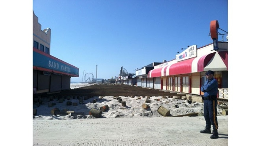 A local police officer stands guard as a new boardwalk is installed along the beach in Seaside Heights, NJ