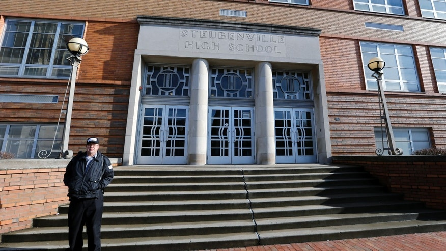 FILE - In this file photo from Jan. 9, 2013, a security guard stands near the entrance to Steubenville High School in Steubenville, Ohio. Ohio Attorney General Mike DeWine said on Thursday April 25, 2013 that search warrants have been executed at the high school attended by the two football players convicted in this trial. DeWine's office says in a statement that search warrants were also executed Thursday at the Steubenville school board offices and a northeast Ohio digital investigations company. (AP Photo/Keith Srakocic, File)