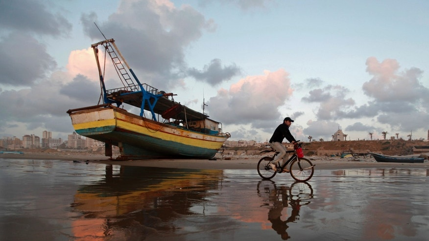 A Palestinian man rides a bicycle on the beach of Gaza City during sunset on Tuesday. April 9, 2013. (AP Photo/Hatem Moussa)