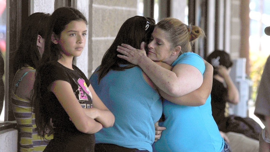 In a Sunday, April 28, 2013 photo, Valley Springs residents Stacey Sims, right, comforts fellow resident Amanda Pekarek, who both knew the 8 year old murder victim Leila Fowler, who was friends with their children, after a press conference outside the Sheriff's substation in Valley Springs on Sunday. Fowler was stabbed to death on Saturday at the home in Valley Springs, Coroner Kevin Raggio said. (AP Photo/The Modesto Bee, Elias Funez) LOCAL TV OUT (KXTV10, KCRA3, KOVR13, FOX40, KMAX31, KQCA58, CENTRAL VALLEY TV); LOCAL PRINT OUT (TURLOCK JOURNAL, CERES COURIER, OAKDALE LEADER, MODESTO VIEW, PATTERSON IRRIGATOR, MANTECA BULLETIN, RIPON, RECROD, SONORA UNION DEMOCRAT, AMADOR LEDGER DISPATCH, ESCALON TIMES, CALAVERAS ENTERPRISE, RIVERBANKS NEWS) LOCAL INTERNET OUT (TURLOCK CITY NEWS.COM, MOTHER LODE.COM)