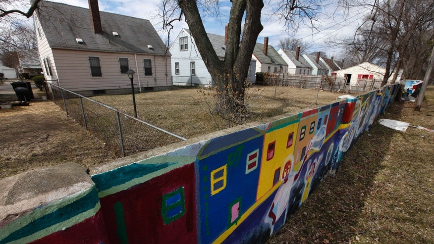 A section of a half-mile long concrete wall, six feet tall and a foot or so thick, now covered with murals, built in the 1940s is shown in Detroit, March 28, 2013. The wall was built with a simple aim: separate homes planned for middle-class whites from blacks who had already built small houses or owned land with plans to build in the neighborhood.It couldn't separate people on its own, people and policies would see to that, but it was enough to satisfy the Federal Housing Administration to approve and back loans. (AP Photo/Paul Sancya)