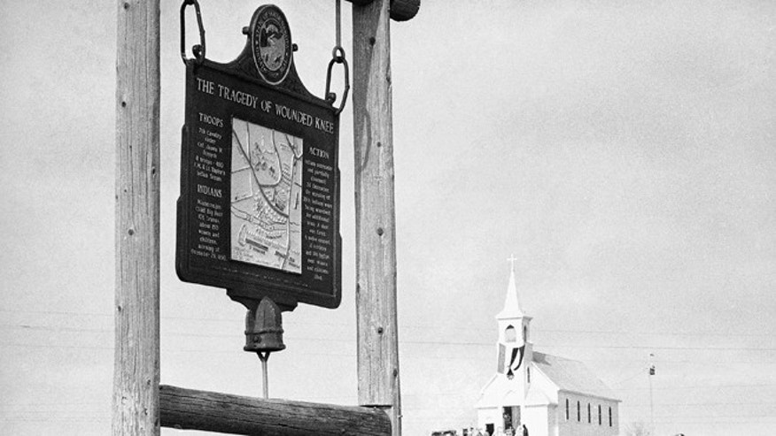 This undated file photo shows the historical marker commemorating the Wounded Knee Massacre of 1890 on the road near the Sacred Heart Catholic Church in Wounded Knee, S.D.