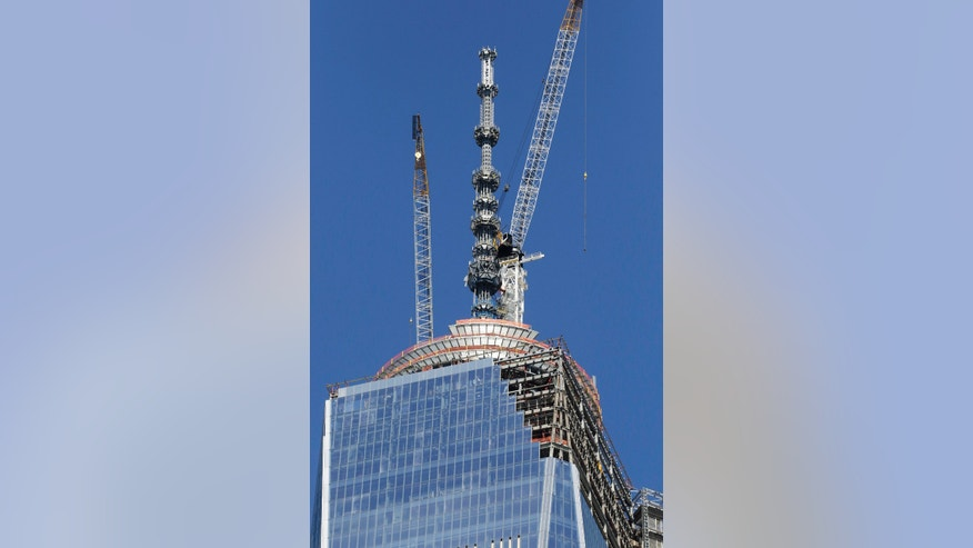 Cranes work adjacent to the spire on top of One World Trade Center, Wednesday, May 1, 2013 in New York. The last piece of spire will be hoisted to the roof on Thursday, weather permitting, according to a spokesperson for the Port Authority of New York and New Jersey. (AP Photo/Mark Lennihan)