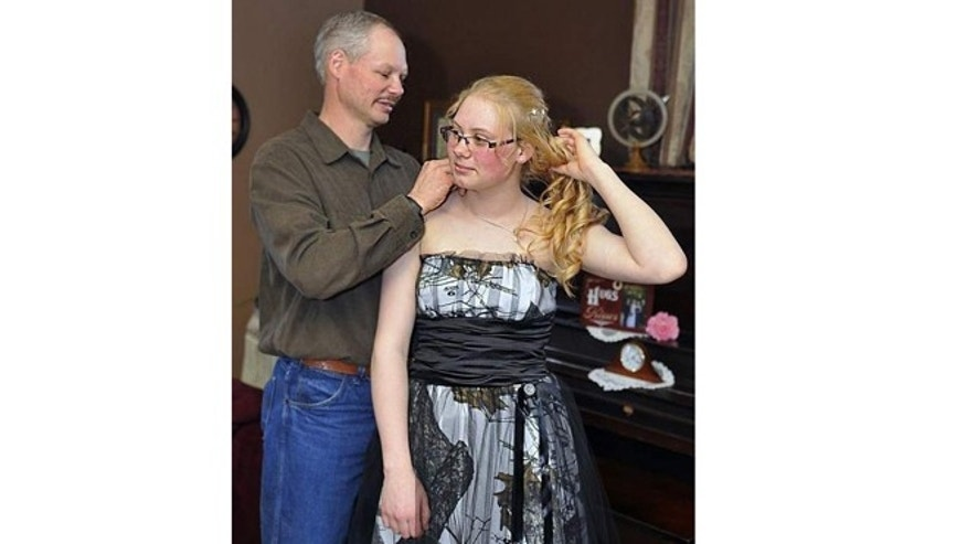 David Herron made a camouflage prom dress for his youngest daughter, Mariah, 17, in Marshfield, Wis.