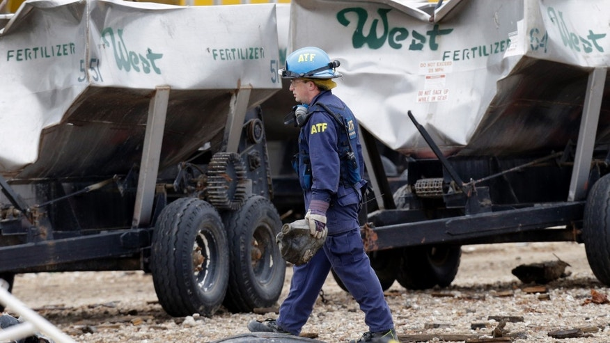 An investigator carries a piece of debris amid the destroyed fertilizer plant in West, Texas, Thursday, May 2, 2013. Investigators face a slew of challenges in figuring out what caused the explosion at the fertilizer plant that killed 14 people and destroyed part of the small Texas town. (AP Photo/LM Otero, Pool)