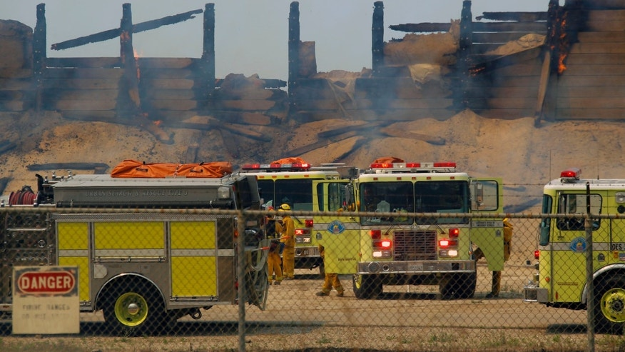 Fire trucks keep an eye on a burned structure at the Naval Base Ventura County (NBVC) at Point Mugu, Calif., Friday, May 3, 2013. The 15 1/2-square-mile blaze was only 10 percent contained on Friday, and the work of more than 900 firefighters, aided by air tankers, was just beginning. (AP Photo/Nick Ut)