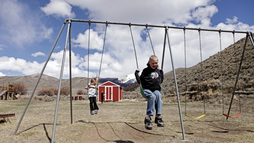 In this April 30, 2013 , photo, siblings, Tyrell and Shelby Schrepfer swing at recess in Polaris, Montana. The pair are students at Polaris School, which only serves four students. (AP Photo/Kathryn Haake)