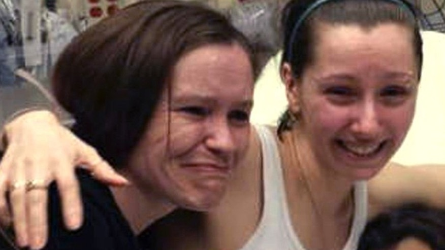 May 6: Amanda Berry, right, hugs her sister Beth Serrano after being reunited in a Cleveland hospital.