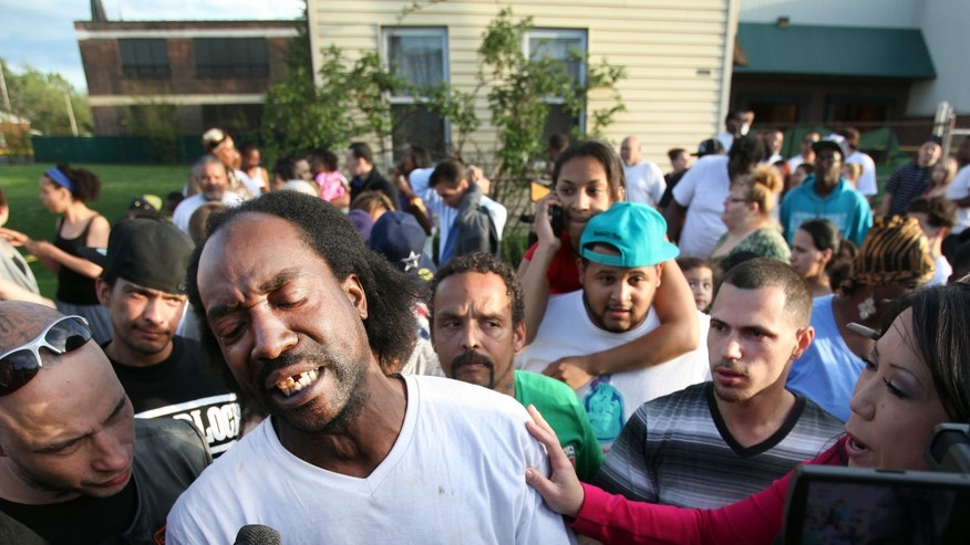 Neighbor Charles Ramsey speaks to media near the home on the 2200 block of Seymour Avenue, where three missing women were rescued in Cleveland, on Monday, May 6, 2013. Cheering crowds gathered on the street where police said Amanda Berry, Gina DeJesus and Michele Knight, who went missing about a decade ago and were found earlier in the day. (AP Photo/The Plain Dealer, Scott Shaw) MANDATORY CREDIT CLEVELAND PLAIN DEALER