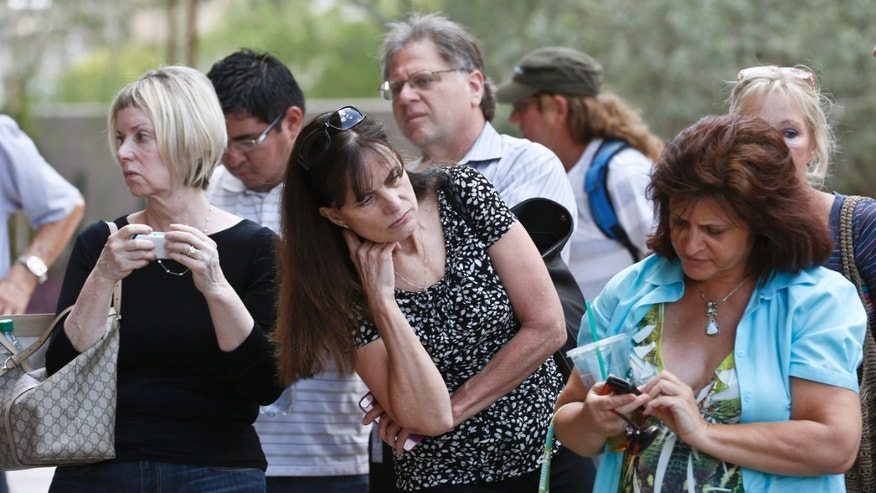 Curious onlookers check their cellphones and listen in on conversations in front of Maricopa County Superior Court Monday, May 6, 2013, in Phoenix. A Phoenix jury is on its second day of deliberations in the trial of Jodi Arias, who is accused of murdering her one-time boyfriend in Arizona. (AP Photo/Ross D. Franklin)
