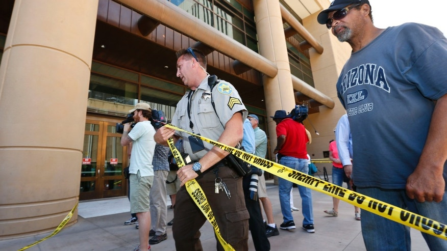 A Maricopa County Sheriffs deputy clears off part of the entrance in front of Maricopa County Superior Court building with police tape, as the crowd waits for a verdict in the Jodi Arias murder trial, Tuesday, May 7, 2013, in Phoenix.  A Phoenix jury is on its third day of deliberations in the trial of Jodi Arias, who is accused of murdering her one-time boyfriend, Travis Alexander, in Arizona. (AP Photo/Ross D. Franklin)