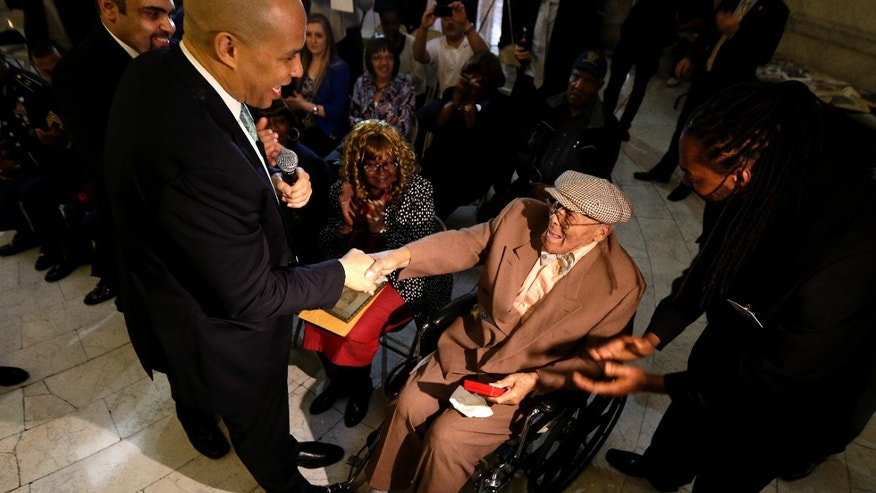 Newark Mayor Cory Booker, left, shakes hands with Willie Wilkins after returning a box with Wilkins World War II dog tags, which he lost in France during the war, at an event to return them to the veteran, Wednesday, May 8, 2013, in Newark, N.J. The U.S. Army tags were lost in 1944 and were found by Anne-Marie Crespo, a resident of Istres, France, who was digging in her garden in 2001. The event, which was held as a surprise for Wilkins, 90, also marked the 68th anniversary of V-E Day, the end of World War II in Europe. (AP Photo/Julio Cortez)