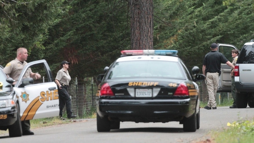 Shasta County Sheriff's deputies investigate the scene of a triple homicide Wednesday, May 8, 2013 in Shingletown, Calif. Authorities in rural Northern California on Wednesday were searching for a man suspected of fatally shooting his wife and two young daughters at their home. Shane Franklin Miller, 45, was on the loose a day after the killings in Shingletown, Shasta County sheriff's officials said. (AP Photo/Record Searchlight, Andreas Fuhrmann)