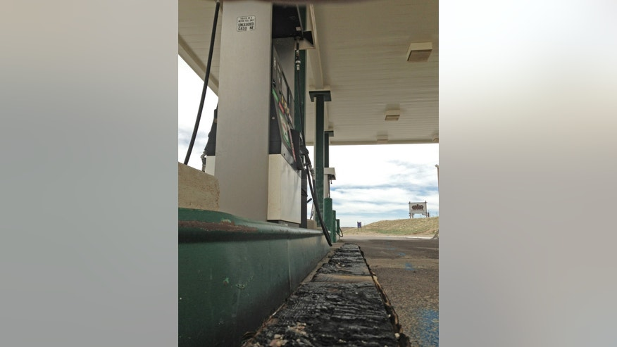 This April 29,2013 photo shows a charred beam that was all that remained of the Horton's Corner convenience store in Chugwater, Wyo., after a Dec. 30, 2012 fire caused by a sport utility vehicle that crashed into the store. Horton's Corner was the only place for miles around to get gas or groceries and may not be rebuilt for several months yet. (AP Photo/Mead Gruver)