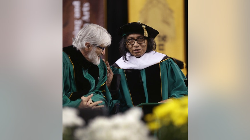 """Wayne State University Board of Governors Paul Massaron, left, talks with Sixto Rodriguez after Rodriguez received a Doctor of Humane Letters honorary degree, Thursday, May 9, 2013 in Detroit, during the university's commencement ceremony. Rodriguez's two albums in the early 1970s received little attention in the United States but he unknowingly developed a cult following in South Africa during the apartheid era. He was the subject of an Oscar-winning documentary, """"Searching for Sugar Man."""".(AP Photo/Carlos Osorio)"""