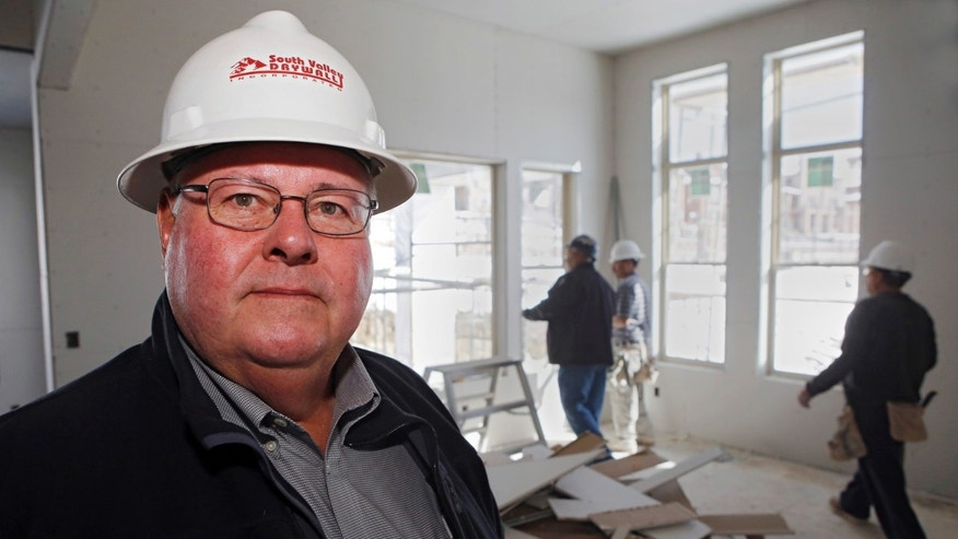 In this April 24, 2013 photo, Richard Vap, owner of South Valley Drywall, poses for a photo at a home construction site with one of his crews working in the background in Lakewood, Colo. The resurgent U.S. housing market has sent builders calling again for Vap, but Vap says he is having trouble hiring enough qualified people. (AP Photo/Ed Andrieski)