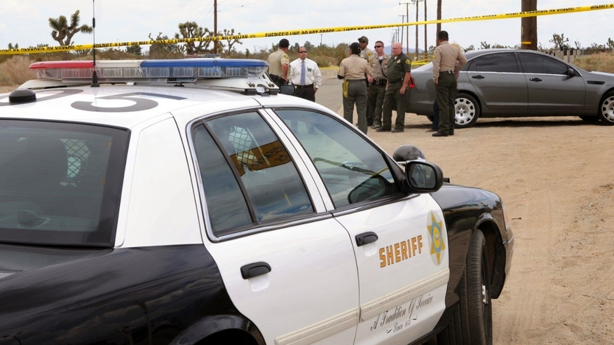Los Angeles County Animal Care and Control and Sheriff personnel congregate near the area where a 63-year-old female jogger was attacked and killed by four pit bulls near Avenue S and 115th Street East in Palmdale, Calif. Sheriff's Lt. John Corina told reporters that a woman in a car saw the dogs attacking the jogger Thursday morning. The witness called 911 and honked her horn to try to get the dogs to stop. (AP Photo/The Antelope Valley Press, Ron Siddle)