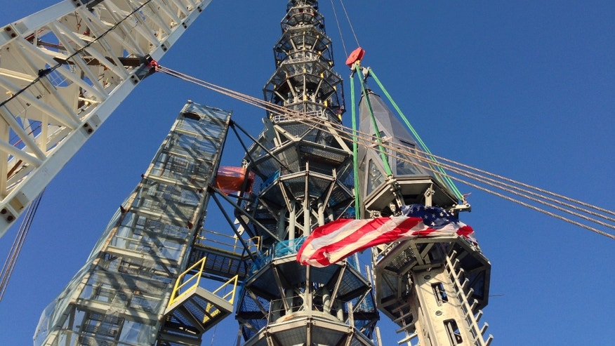 March 10, 2013: Workers prepare to raise the silver spire atop the 1 World Trade Center building in New York early.