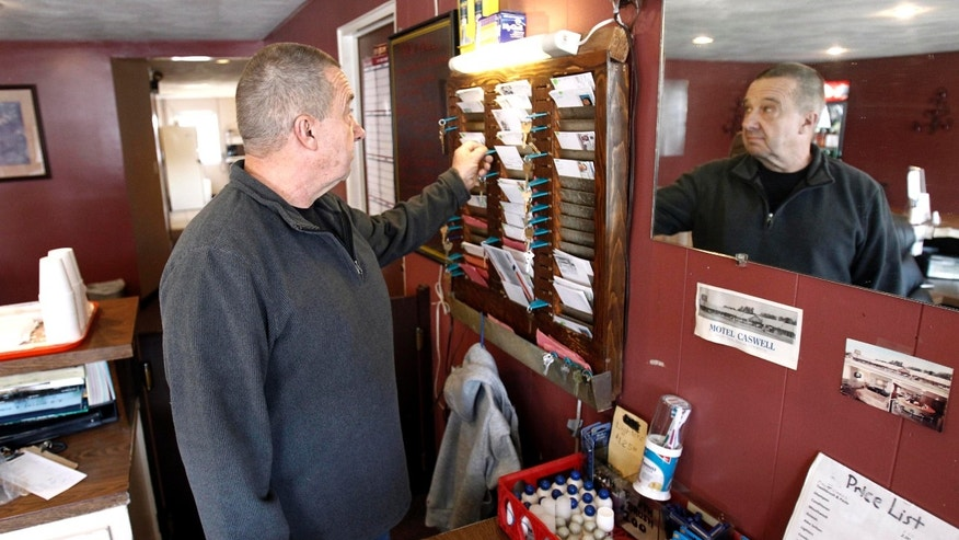 FILE - In this Wednesday, Nov. 9, 2011 file photo, owner Russ Caswell reaches for a room key behind the front desk of the Motel Caswell in Tewksbury, Mass. Caswell is fighting to keep the federal government from taking his motel under a law that allows for forfeiture of properties connected to crimes. The government does not claim that Caswell committed any crimes, but claims there is drug-dealing among the motel's guests.  (AP Photo/Winslow Townson, File)