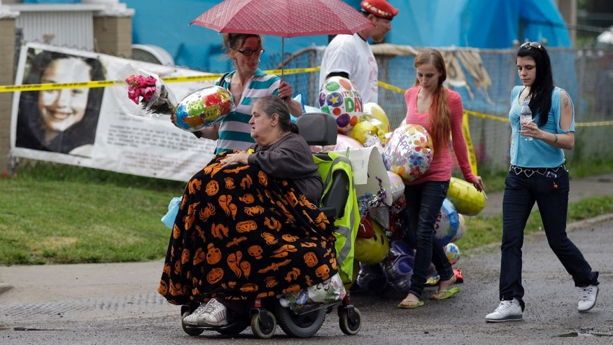 Deborah Knight, grandmother of Michelle Knight, drives her wheelchair past the home of Gina DeJesus in Cleveland Friday, May 10, 2013. Michelle Knight was freed from the home of Ariel Castro along with DeJesus and Amanda Berry Monday where the 52-year-old man had held them captive for a decade. (AP Photo/Mark Duncan)