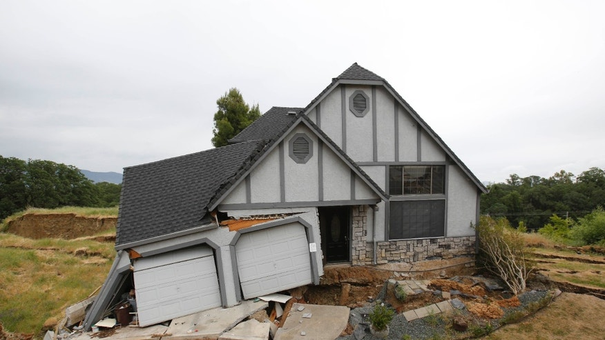 May 6, 2013: This photo shows the wreckage of the Tudor-style dream home of Robin and Scott Spivey who were forced to abandon after the ground gave way causing it to drop 10 feet below the street in Lakeport, Calif.