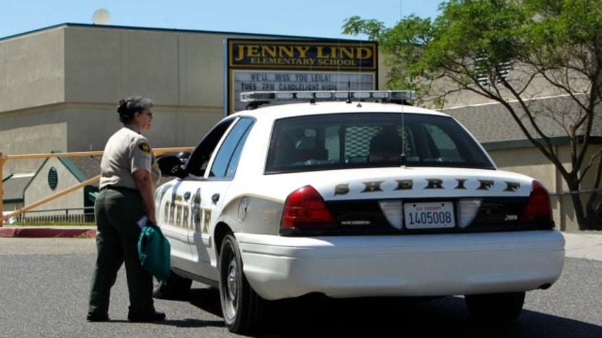 April 29, 2013: Calaveras County Sheriff's deputies and volunteers stand watch at Jenny Lind Elementary School, after the murder of one it's students over the weekend, in Valley Springs, Calif.