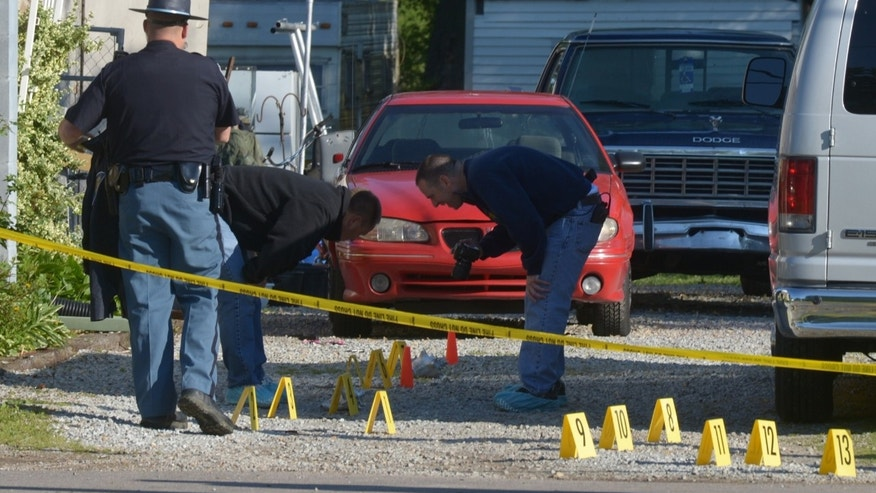 Investigators comb the area in and around 2634 Main Cross Street in Waynesville, Ind., Sunday, May 12, 2012, the scene of a quadruple homicide overnight. (AP Photo/The Republic, Joe Harpring)