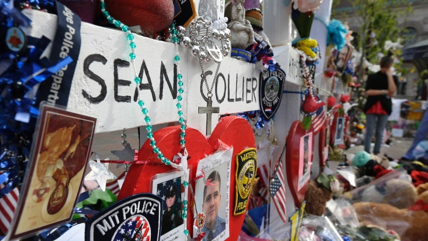 Photographs of slain Massachusetts Institute of Technology campus officer Sean Collier, center, are part of a makeshift memorial near the Boston Marathon finish line in Boston&#39&#x3b;s Copley Square Tuesday, May 7, 2013 in remembrance of the Boston Marathon bombings. Authorities allege that the Boston Marathon bombing suspects were responsible for Colliers death. (AP Photo/Steven Senne)