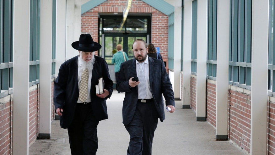 Yosef Kolko, 39, right, walks with an unidentified man, near the Ocean County Courthouse in Toms River, N.J., Thursday, May 9, 2013, during a break in his trial on sexual assault charges. Testimony continues in the trial of the yeshiva teacher accused of sexually abusing a boy at a summer camp where he was a counselor. Prosecutors say the boy's parents were pressured by members of their Orthodox Jewish community to drop the charges and let a rabbinical court deal with them. (AP Photo/Mel Evans)