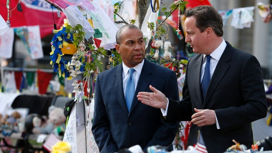 British Prime Minister David Cameron, right, and Massachusetts Gov. Deval Patrick visit the makeshift memorial to the Boston Marathon bombing victims in Copley Square in Boston, Tuesday, May 14, 2013. Cameron is in Boston to offer his condolences and discuss lessons that can be learned from the deadly bombings. (AP Photo/Michael Dwyer)