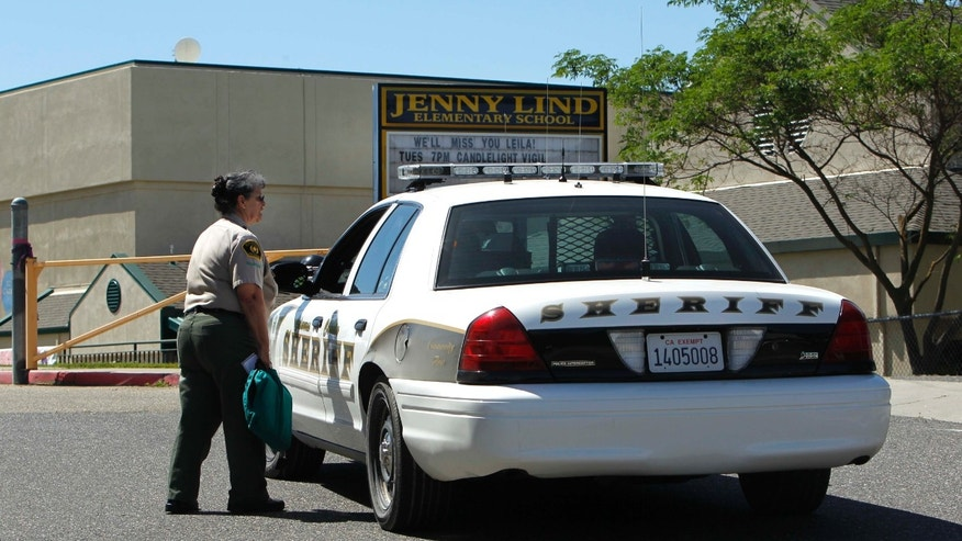 FILE - In this April 29, 2013 file photo, Calaveras County Sheriff's deputies and volunteers stand watch at Jenny Lind Elementary School, after the murder of one it's students over the weekend, in Valley Springs, Calif. Authorities on Saturday, May 11, 2013 arrested the 12-year-old brother of an 8-year-old girl who was mysteriously stabbed at her home in a quiet Northern California community last month. (AP Photo/Rich Pedroncelli, File)