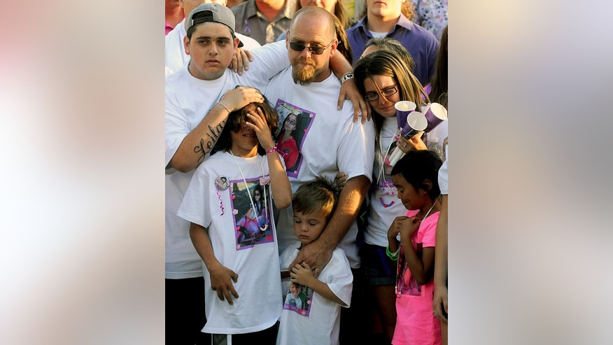 "File - In this Tuesday, April 30, 2013 file photo, the family of slain 8-year-old girl Leila Fowler attend a vigil held for her at Jenny Lind Elementary School in Valley Springs, Calif.  Leila's father, Barney Fowler, center, stands with Leila's mother Crystal Walters, right, at his shoulder. The father of a 12-year-old boy arrested in the stabbing death of his 8-year-old sister says he believes his son is innocent until he is shown evidence that proves otherwise. Barney Fowler said on Monday May 13, 2013 that the family is standing behind the boy ""until they have the proper evidence to show it's my son."" Sheriff's deputies in the Central California foothill community of Valley Springs arrested the 12-year-old on Saturday in the April 27 death of 8-year-old Leila Fowler. (AP Photo/The Modesto Bee, Elias Funez, File)"