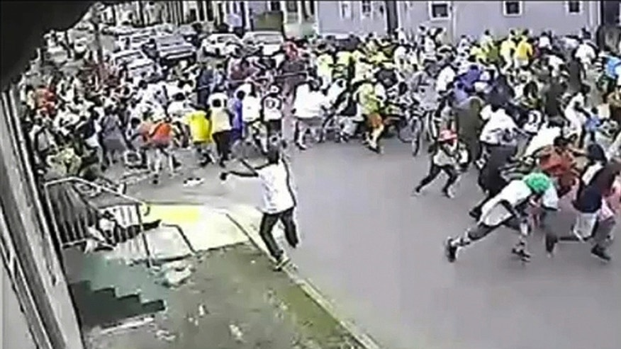 In this image taken from video and provided Monday, May 13, 2013, by the New Orleans Police Department, a possible shooting suspect in a white shirt, bottom center, shoots into a crowd of people, Sunday in New Orleans. Police believe more than one gun was fired in the Mother's Day gunfire that wounded 19 people during a New Orleans neighborhood parade.