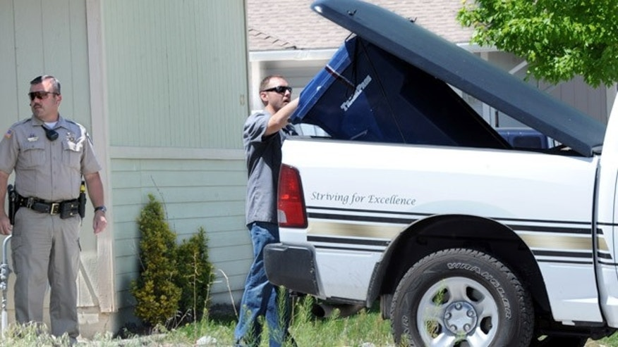 May 14, 2013:  A sealed garbage container is loaded into the back of a Lyon County Sherff's vehicle in Fernley, Nev.