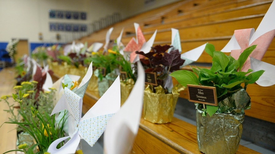 "Flowers and pinwheels with the names of the victims and survivors of the Carrolton bus crash line the seats at North Hardin High School May 14, 2013 in Radcliff, Ky. A quarter century after the nation's deadliest alcohol-related highway crash, the Kentucky town that still grieves for the 27 ""beautiful souls"" who perished on a church bus in the fiery tragedy gathered Tuesday evening to remember the victims and honor the resilience of the survivors. (AP Photo/Timothy D. Easley)"