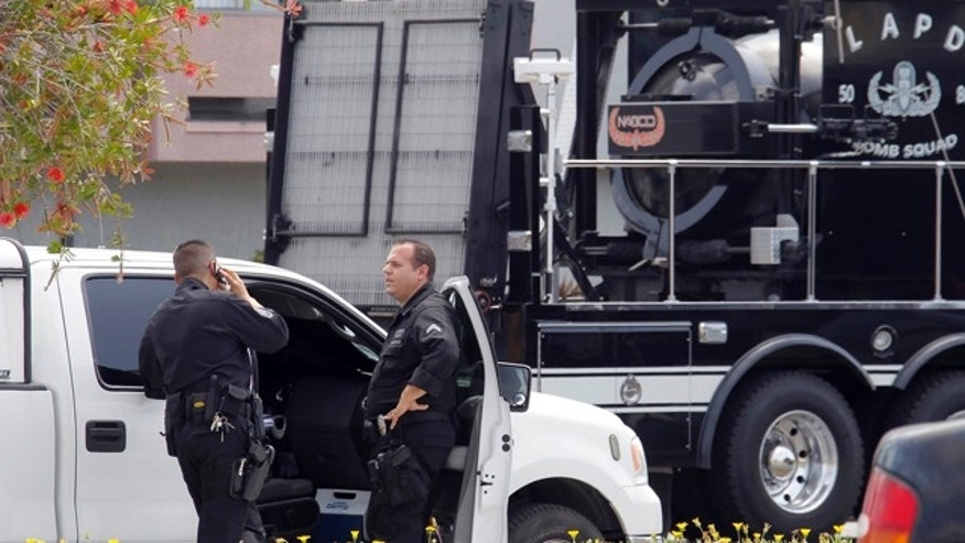May 16, 2013: Los Angeles Police Department bomb squad officers gather at the site where police arrested a man after discovering explosive material in his car and potential explosive devices in his apartment.
