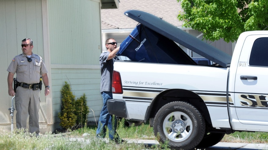 A sealed garbage container is loaded into the back of a Lyon County Sherff's vehicle in Fernley, Nev., Tuesday May 14, 2013. A quiet northern Nevada community is on edge after a spate of killings left five people dead in a single day, including a married couple in their 80s, a 67-year-old woman, and a man found dead not far from the Mustang Ranch brothel. (AP Photo/The Reno Gazette-Journal, Marilyn Newton)
