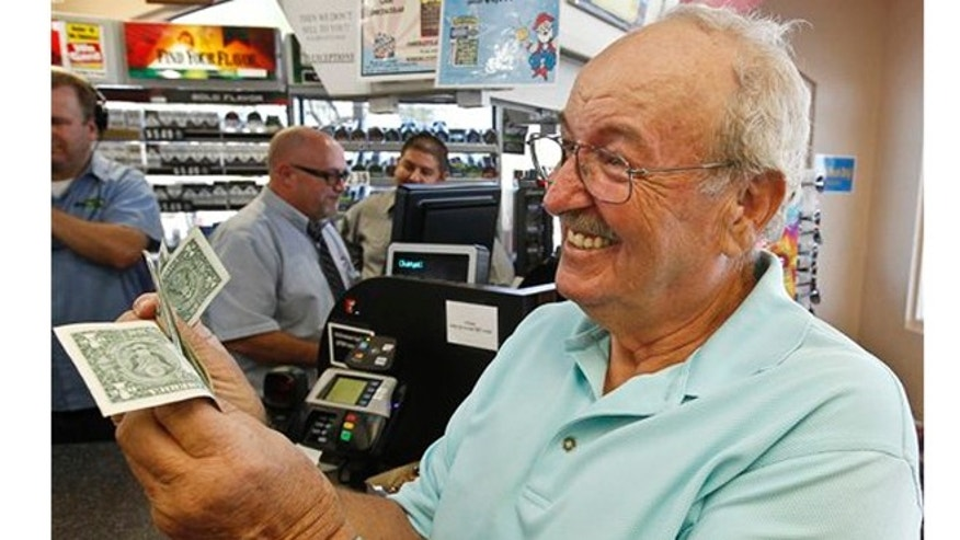 Wes Prinzen, of Fountain Hills, Ariz., smiles as he takes away his modest $4 winnings, at a 4 Sons Food Store where one of the winning tickets in the $579.9 million Powerball jackpot.
